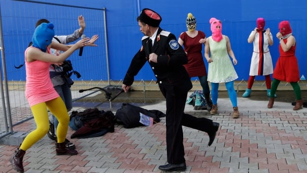 A Cossack militiaman attacks members of the punk group Pussy Riot on Wednesday. The band left Sochi on Thursday by posting a video criticizing the Winter Games and President Vladimir Putin.