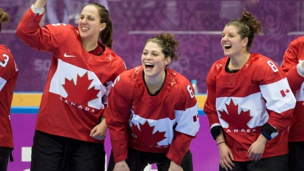 Canada's Laura Fortino, Rebecca Johnston and Lauriane Rougeau, right to left, celebrate after beating the USA 3-2 in overtime to win the gold medal in the women's hockey final at the Sochi Winter Olympics Thursday, February 20, 2014 in Sochi.