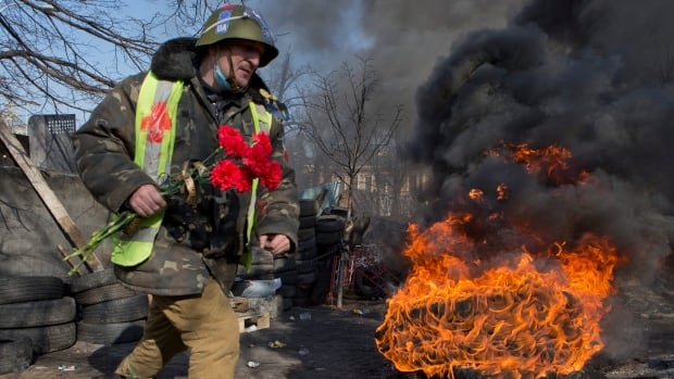 An anti-government protester moves past burning car tires as he carries flowers to be laid at the spot where some of his comrades were killed the previous day, at a barricade in central Kyiv, Ukraine on Feb. 21, 2014. Ratings agency Standard & Poor's says Ukraine will likely default on its debt if there are no significant improvements in the political crisis.