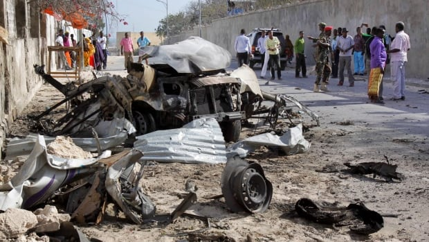 Somalis gather near the wreckage of one of the vehicles used for a car bomb, following a militant attack on the presidential palace in Mogadishu, Somalia.