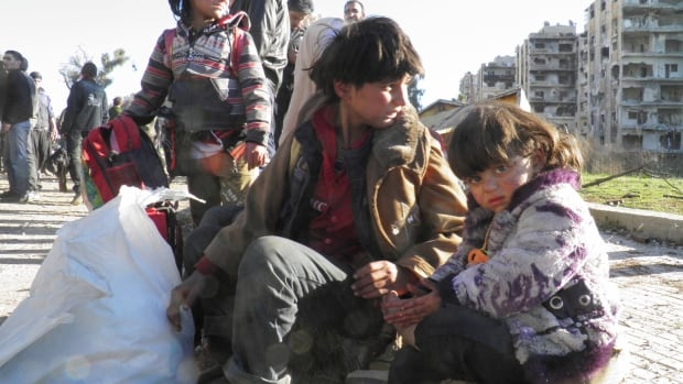 Children sit with their belongings as they wait to be evacuated from a besieged area of Homs on Feb. 12, 2014. UN humanitarian chief Valerie Amos said last week progress on Syria's humanitarian front in the last four months has been 'limited, uneven and painfully slow.'