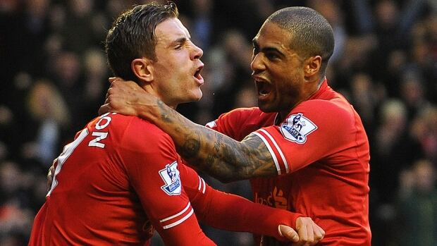 Liverpool's English midfielder Jordan Henderson, left, celebrates scoring his team's fourth goal with defender Glen Johnson during a Premier League matc against Swansea on Sunday. Liverpool prevailed 4-3.