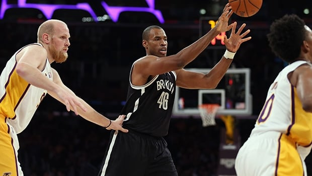 Jason Collins of the Brooklyn Nets, centre, is defended by Chris Kaman of the Los Angeles Lakers in the first half at Staples Center on February 23, 2014 in Los Angeles, California.