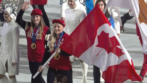 Bobsledders Heather Moyse and Kaillie Humphries, who is from Calgary, carry in the Canadian flag at the closing ceremony of the Sochi 2014 Olympic Winter Games. The pair won another gold medal to follow up their performance in Vancouver.