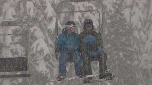 snowboarders riding chairlift