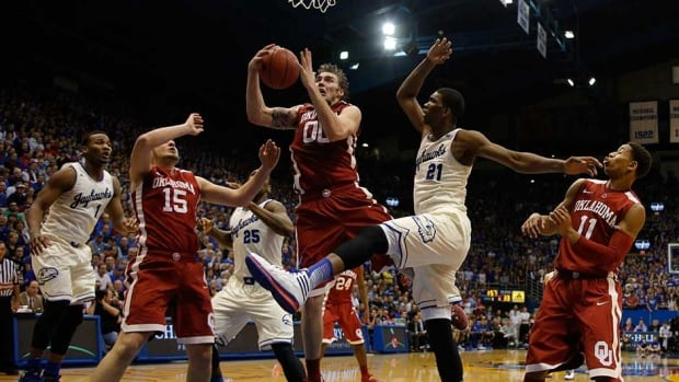 Ryan Spangler (00) of the Oklahoma Sooners grabs a rebound between teammate Tyler Neal (15) and Joel Embiid (21) of the Kansas Jayhawks in the first half at Allen Fieldhouse on Monday in Lawrence, Kansas.