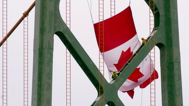Workers battle rain and high winds as they attach a large Canadian flag to the Angus L. Macdonald Bridge spanning the harbour as they prepare for Canada Day last year.