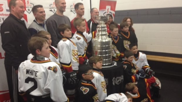 The Fort Garry Red Flyers pose with the Stanley Cup after it showed up in their dressing room Tuesday night.