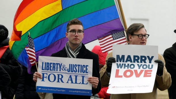 In this Feb. 4, 2014 photo, demonstrators hold signs outside a federal court in Norfolk, Virginia. The state's ban on same-sex marriage was recently ruled unconstitutional and the attorney general said he won't try to defend the ban.