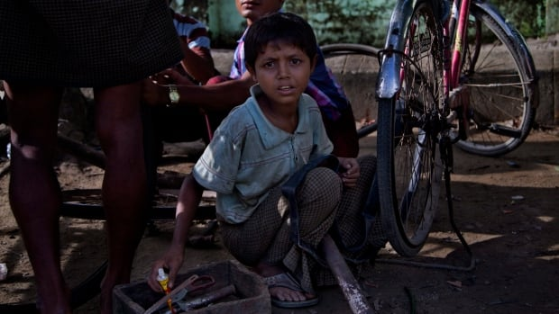 In this photo from Sept. 2013, Inamo Arsong, a 12-year old Muslim boy, repairs bicycles at a sidewalk in Maungdaw, in Myanmar's Rakhine state. Doctors Without Borders says it has been expelled from the country because of its work with the long-persecuted Muslin population.