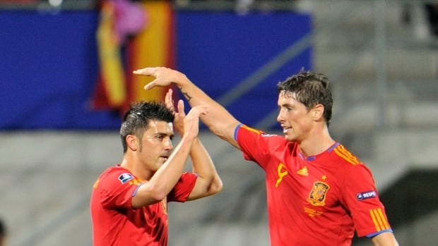 Spanish national team veterans David Villa and Fernando Torres are shown celebrating a goal in a late 2010 match.