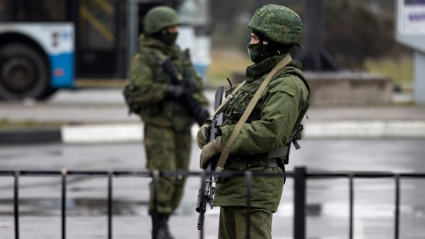 Armed men patrol at the Simferopol airport in the Crimea region.