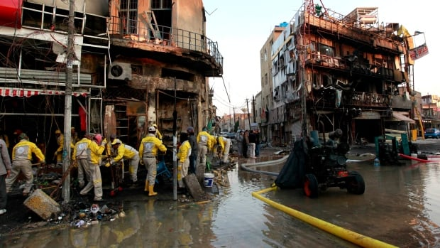 Baghdad municipality workers clean at the site of a car bomb explosion in Baghdad where Shia neighbourhoods have experienced a wave of attacks.