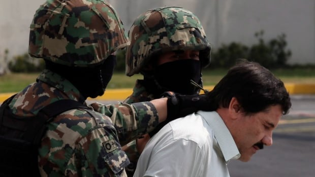 "FILE - In this Feb. 22, 2014, file photo, Joaquin ""El Chapo"" Guzman, in handcuffs, is escorted to a helicopter by Mexican navy marines in Mexico City, Mexico. At least seven U.S. courts have indictments pending against him, and several are pressing for extradition. In Mexico, he faces organized-crime charges in four Mexican states and in Mexico City. He could, barring another escape, spend the rest of his life behind bars. (AP Photo/Dario Lopez-Mills)"