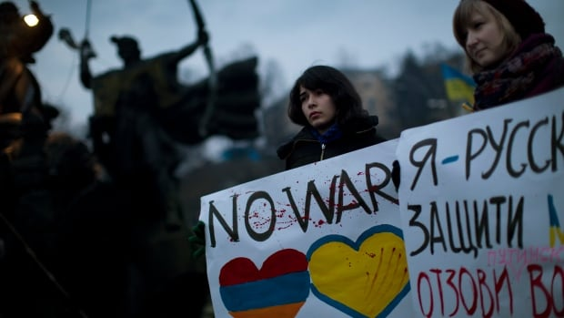 "Ukrainian Maria, 23, right, and Vanui, 22, hold posters against Russia's military intervention in Crimea, in Kyiv, Ukraine, on Sunday. The poster in the right side reads in Ukrainian: ""I am from Russia, please protect me and remove the weapons and soldiers from Ukraine."""