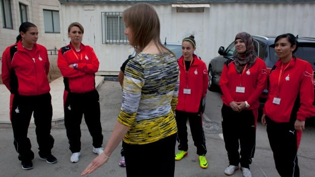 Canadian speedskater Cindy Klassen talks to members from the Palestinian Dar al-Kalima women's soccer team prior to an inauguration ceremony of their women's indoor sports centre in the West Bank city of Bethlehem on Sunday.