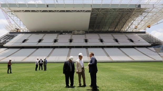Jerome Valcke, secretary general of FIFA, right centre, and Aldo Rebelo, Brazil's sports minister, centre, inspect the Sao Paulo stadium.