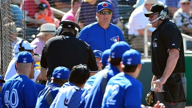 Umpires speak to the replay official after the Toronto Blue Jays manager John Gibbons challenges a play call at first base during the sixth inning against the Twins at Hammond Stadium Monday.