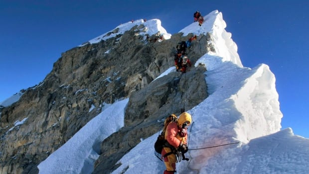 Some 230,000 people — nearly half of Nepal's yearly foreign visitors — came last year specifically to trek the Himalayas, with 810 attempting to scale Everest., including these climbers on the Hillary Step en route to the summit.