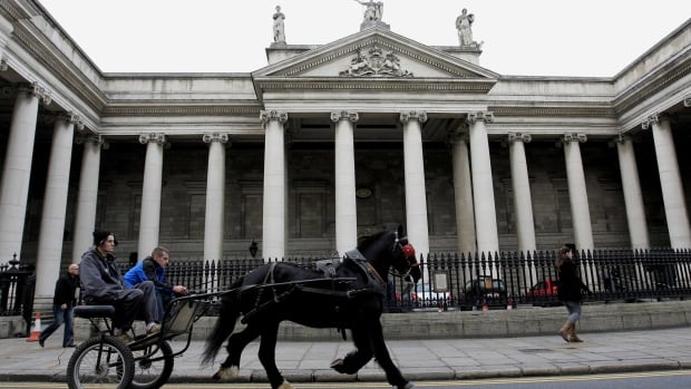 A horse and cart passes the Bank of Ireland in central Dublin, Ireland.  Bank shares have tripled in price since Fairfax Financial bought a stake in 2011.