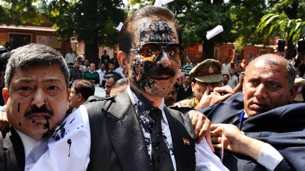 Subrata Roy, chairman of Sahara India Pariwar, was splashed with ink as he headed into court to face fraud charges in New Delhi, India, Tuesday.