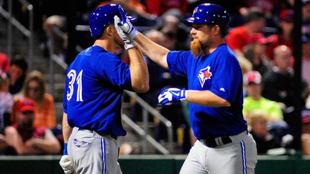 Toronto Blue Jays first baseman Adam Lind (26) is congratulated by catcher Erik Kratz after hitting a solo home run in the fourth inning at Bright House Field on Tuesday.