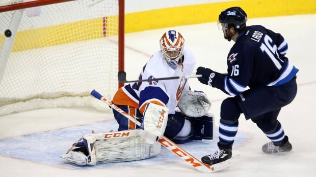 Winnipeg Jets' captain Andrew Ladd scores on New York Islanders goalie Anders Nilsson during third period of Tuesday's game, to tied it up 2-2 and send it to overtime. The Jets lost in O/T 3-2.