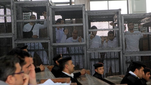 Al-Jazeera English Egypt bureau chief Mohamed Fahmy, an Egyptian-Canadian national, left, producer Baher Mohamed, second left, and correspondent Peter Greste, centre, stand inside the defendants' cages in a courtroom in Tora prison on the outskirts of Cairo. The three have been accused of aiding the Muslim Brotherhood, which Egypt's new government has labelled a terrorist organization.
