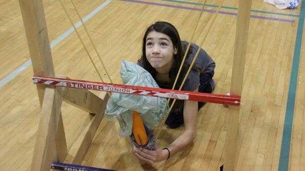 A Grade 6 student at Regina's St. Gabriel School prepares to launch a non-powered rocket on a stretchy line.