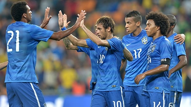 Brazil's Neymar, centre, celebrates with teammates after scoring against South Africa at Soccer City stadium in Soweto, outside Johannesburg, on March 5, 2014.