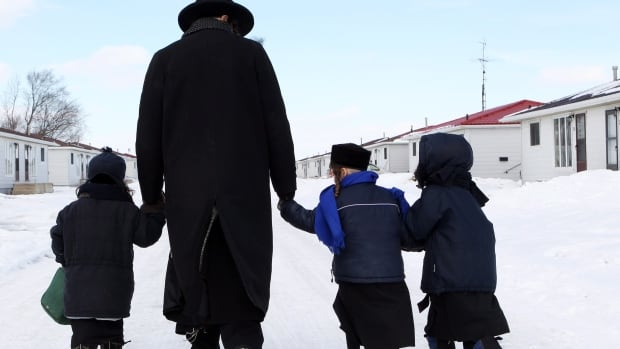Members of the Lev Tahor ultra-orthodox Jewish sect walk down a street in Chatham, Ont. They have since departed for Trinidad and Tobago, which now appears ready to send them back to Canada.