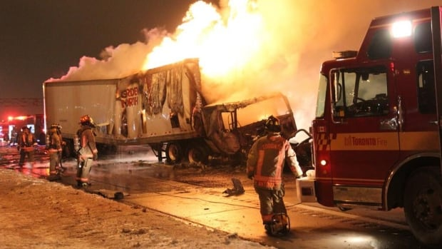 Fire crews work to clean up a collision involving two tractor-trailers on Highway 401 just west of Highway 427 early Thursday.