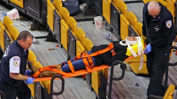 Emergency workers remove an injured woman from TD Garden after suffering injuries when a metal pole holding up protective netting behind one of the goals fell, after a Boston Bruins game on Thursday.