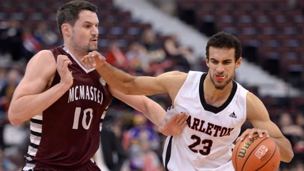 Carleton Ravens' Philip Scrubb, right, drives the ball past McMaster Marauders' Taylor Black in Ottawa on Friday, March 7, 2014.