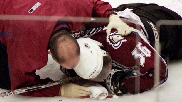 In this March 7, 2004, file photo, Colorado Avalanche forward Steve Moore is attended to by the team trainer after being injured in an incident with Vancouver Canucks Todd Bertuzzi. The on-ice attack that ended Moore's NHL career.