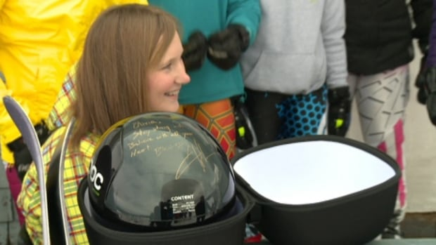 Olivia McLean sits with a helmet signed by Canadian Olympic bronze medal winner Jan Hudec. McLean survived a major ski accident three weeks ago thanks to a helmet that saved her life.