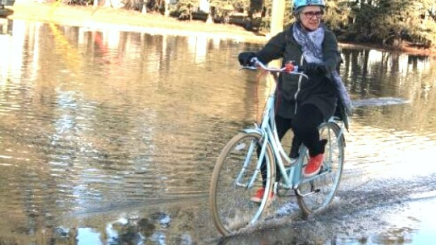 A cyclist rides through Crescent Road and Seven A Street N.W., one of the many flooded roads being reported across Calgary.