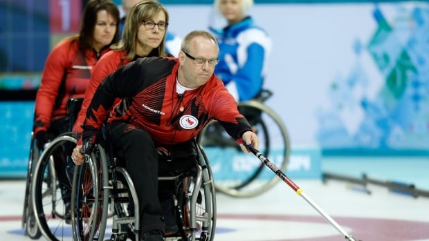 Canada's Dennis Thiessen throws a rock during wheelchair curling round-robin play at the Sochi Paralympics.