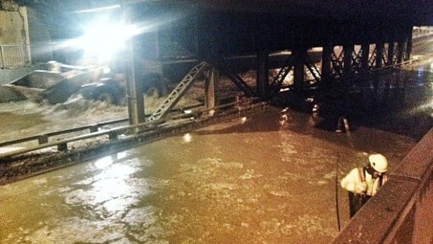 Crews work on a water main break at McPhillips Street underpass on Monday.