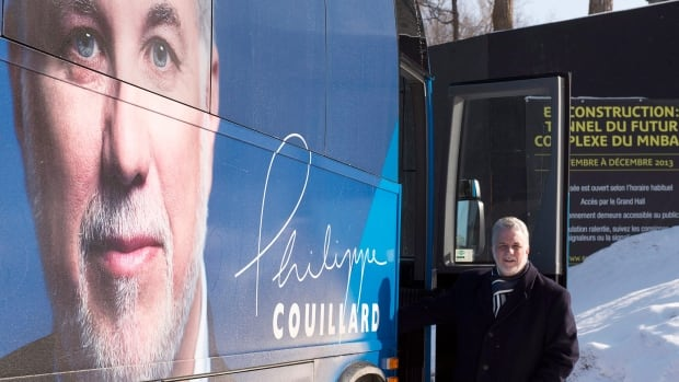 Quebec Liberal Party Leader Philippe Couillard hops on his campaign bus after a news conference on education in Quebec City.