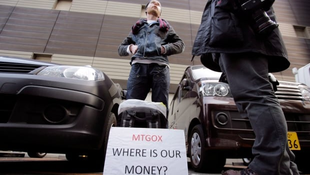 A disgruntled bitcoin trader protests outside Mt. Gox offices in Tokyo. The bitcoin exchange, which is facing numerous lawsuits over the loss of hundreds of thousands of customers' bitcoins, has received bankruptcy protection in Japan and the U.S., which has stalled legal action pending against the Japanese company.