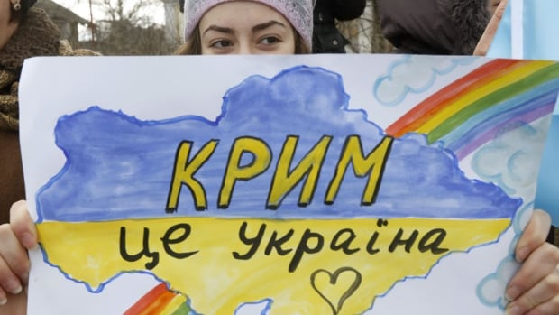 A girl holds a drawing during an anti-war rally in the Crimean village of Eskisaray, outside Simferopol, March 10. 2014.
