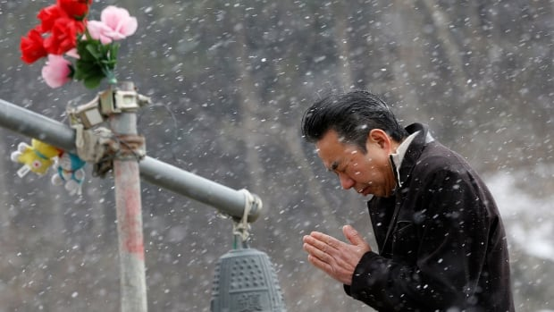 A man prays outside a school where 74 of 108 students went missing after the March 11, 2011 tsunami in northern Japan.  Japan on Tuesday marks the third anniversary of the earthquake and tsunami that killed 15,884 people and left more than 2,600 unaccounted for in vast areas of its northern coast.
