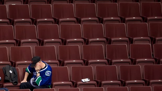 A Vancouver Canucks fan sits in the stands after the team gave up seven goals to the New York Islanders in the third period and lost 7-4 in Vancouver on Monday.
