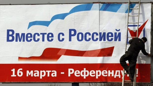 "A worker puts up a poster that reads, ""Together with Russia. March 16 - referendum"", in the centre of Simferopol, the Crimean capital."