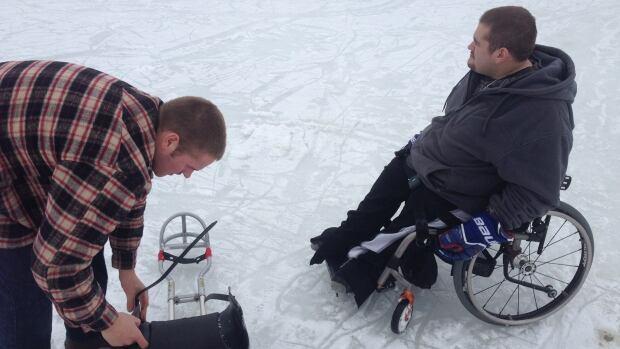 Sledge hockey players Jesse and Brandon Raymond on the ice at Ramsey Lake.