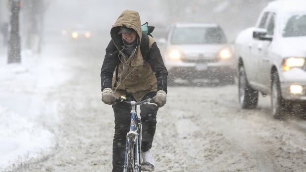 A bike messenger slogs through slush on John Street in downtown Toronto on March 12. More than 10 centimetres of heavy, blowing snow blanketed the city, closing schools, delaying flights and causing chaos on the roads.