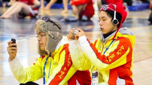 Young athletes from Team Nunavut enjoyed their gadgets at the 2012 Arctic Winter Games in Whitehorse. This year, Team Yukon's social media liaison is forecasting an even bigger 'social media frenzy.'