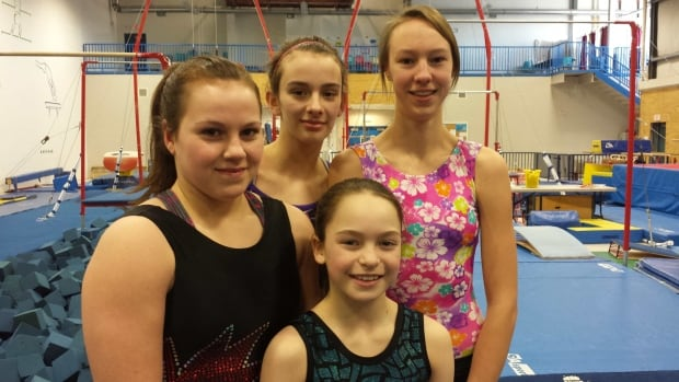 Maggie Carson, front, poses with her teammates Rana Jalil Aga and Hailey Tait, and former Arctic Winter Games gymnastics medallist Celena Hoeve in the Yellowknife gymnastics club.