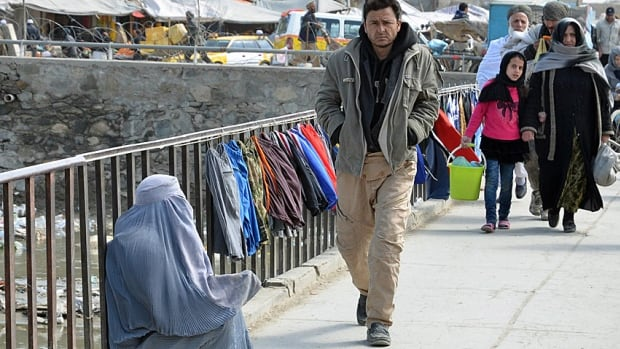 A woman begs for change on Kabul's Yakpesagi (One Penny) Bridge on Monday, March 10, 2014. The accelerating withdrawal of NATO and Canadian military forces has led to business uncertainty and fears of a post-war economic collapse.